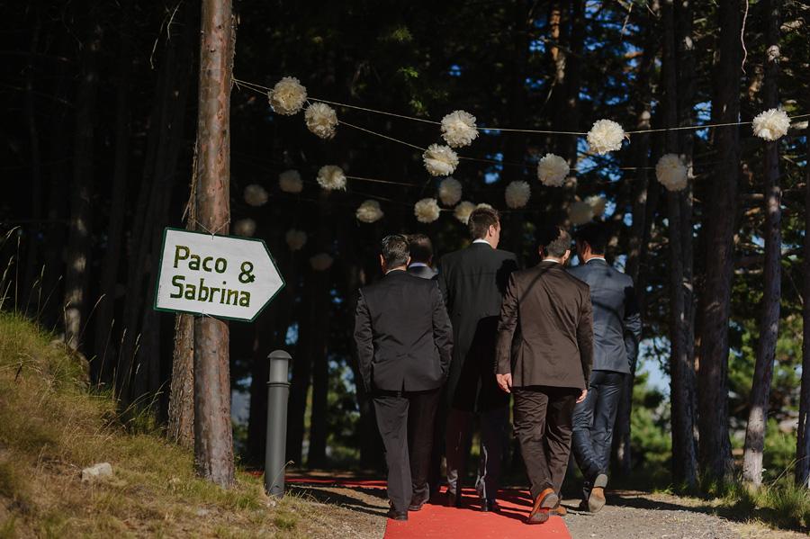 el novio camina hacia la ermita acompañado de sus amigos, un cartel con el nombre de los novios indica la direcció