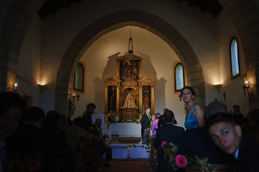 el novio espera a la novia en el altar iluminado por un rayo de sol que entra por la puerta