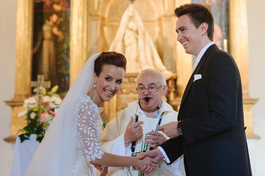 pareja de novios riendo en el altar, el cura muy simpático haciendo amena la ceremonia