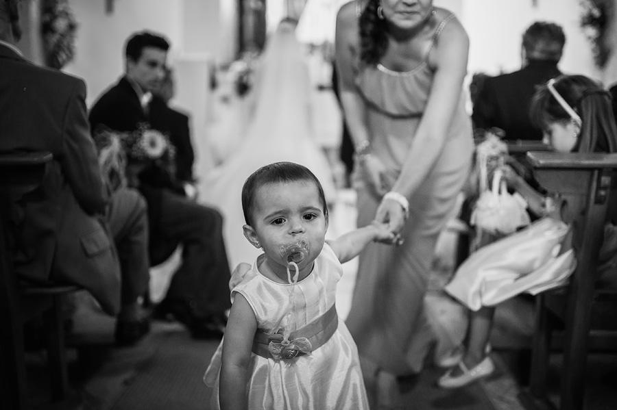una niña pequeña con chupete quiere salir de la iglesia de la mano de su madre