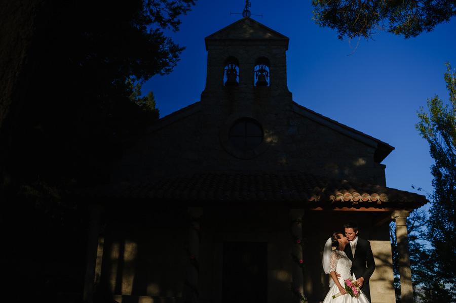 los novios frente a la fachada de la iglesia, iluminados con por un rayo de sol el atardecer