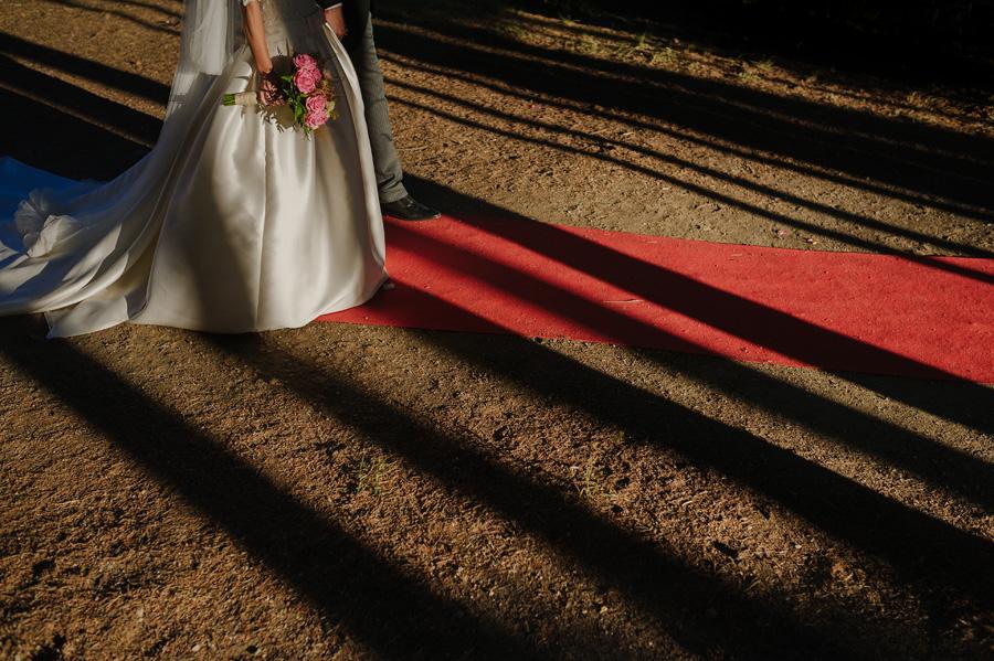 vestido de la novia con el ramo de rosas, la luz del atardecer ilumina la escena y crea sombras al pasar entre los arboles