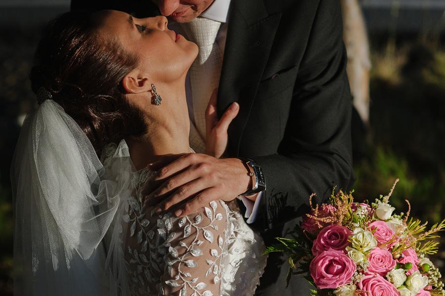 pareja de novios, a punto de besarse, iluminados por la luz del atardecer, la novia sujeta la solapa del novio