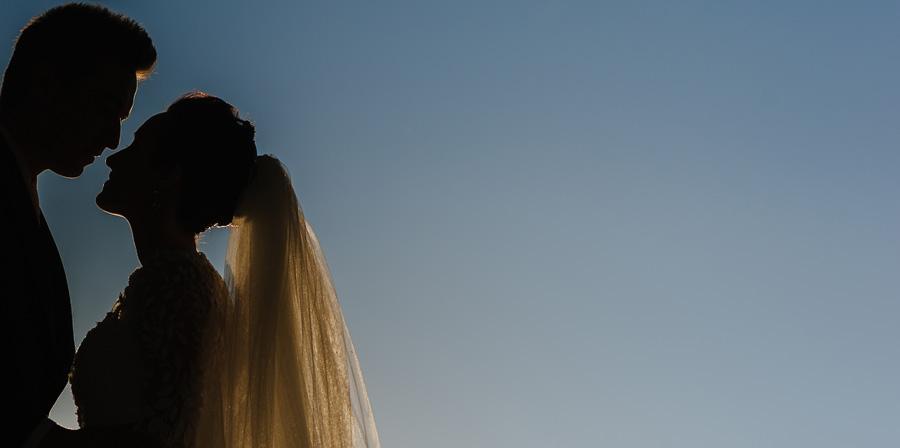 silueta de los novios mirandose a los ojos, perfilados por la luz del atardecer