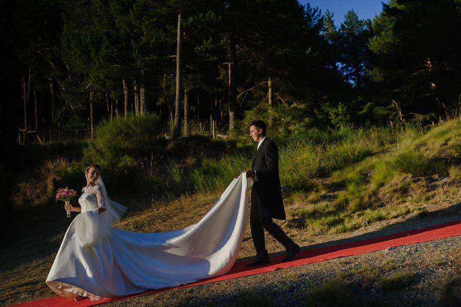 el novio ayuda a la novia sujetando su vestido mientras la novia con el ramo mira hacia atras y le sonrie