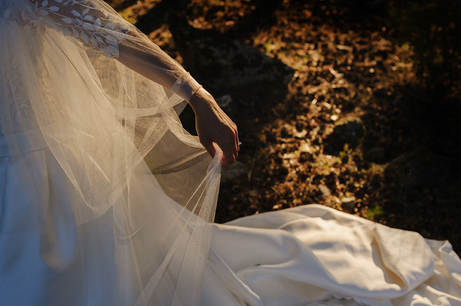detalle del vestido y velo velo de la novia iluminado por la luz del atardecer