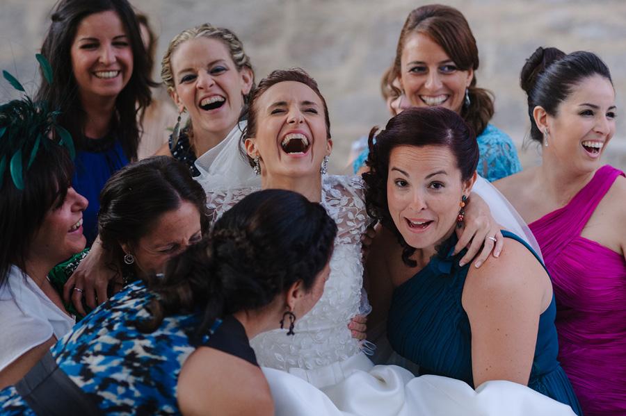 la novia con una gran carcajada rodeada de sus amigas sonrientes