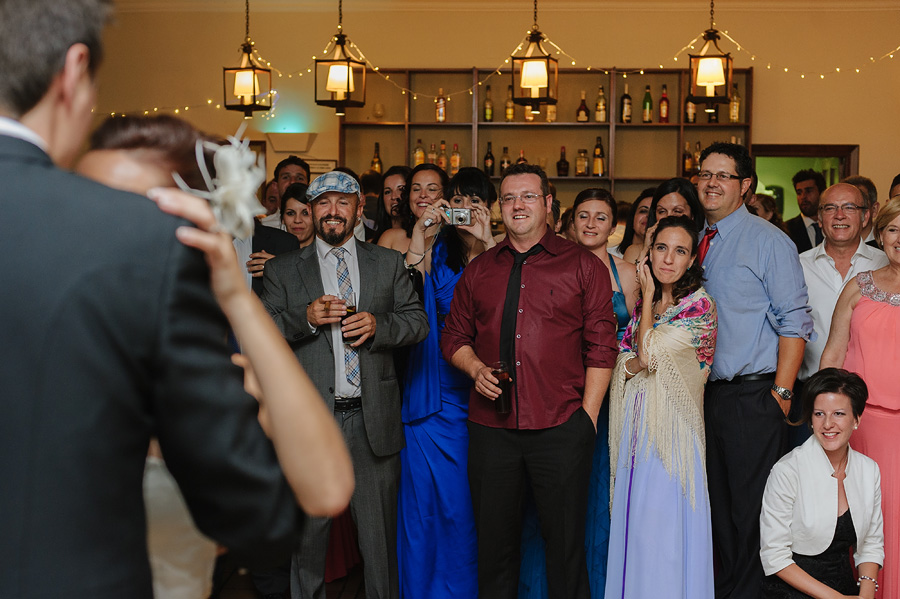 los invitados miran el primer baile de los novios y sonrien