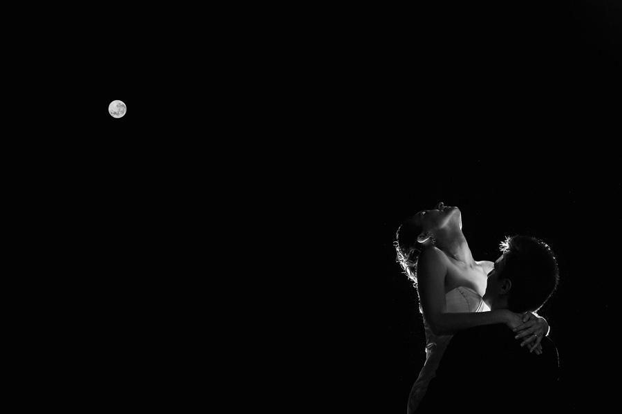 el novio levanta a la novia por la cintura de noche con la luna llena de fondo