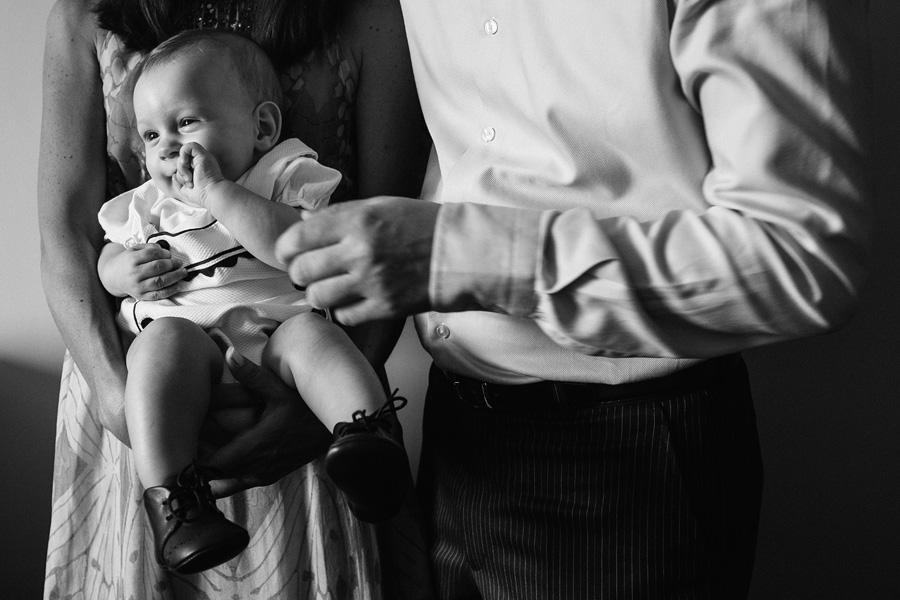 fotos de bautizo, bautizo en madrd, los tios del bebe lo tienen en brazos y el bebe sonrie con la mano en la boca