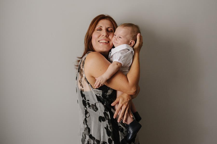 fotos de bautizo, bautizo en madrd, la mama abraza cariñosamente a su hijo, que sonrie