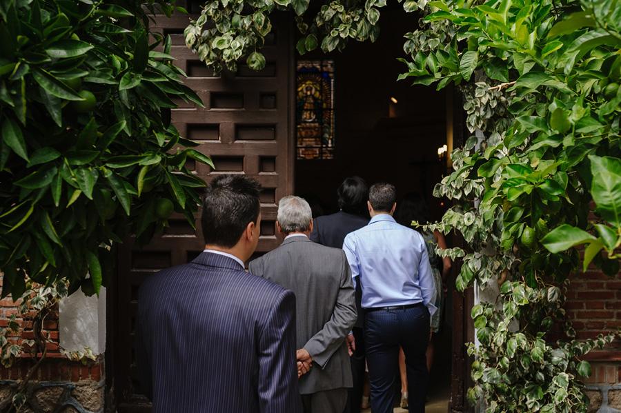 fotos de bautizo, bautizo en madrd, fotografo de bautizo, los familiares y amigos entrar en la iglesia, la puerta esta rodeada de plantas