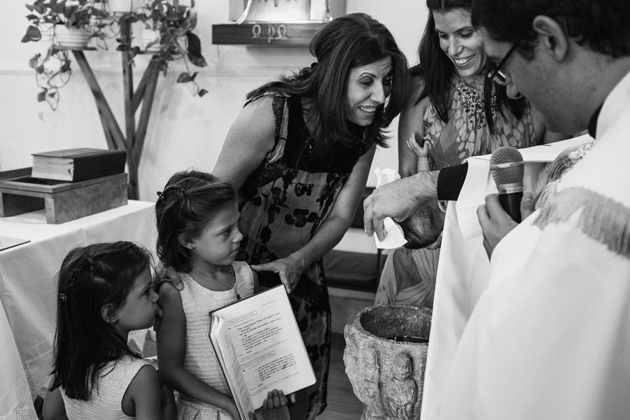 fotos de bautizo, bautizo en madrd, fotografo de bautizo, mama sonríe a su bebe que acaba de ser bautizado, sus primas ayudan al párroco sujetando la biblia