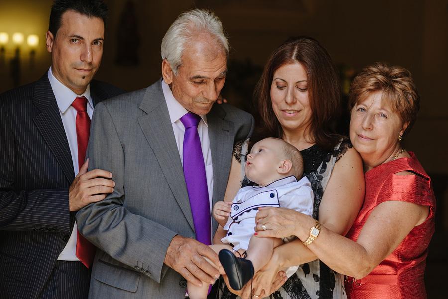 fotos de bautizo, bautizo en madrd, fotografo de bautizo, foto de familia, mama con su bebe en brazos que mira al abuelo, la abuela junto a su hija y el hermano al lado del abuelo
