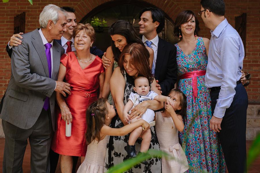 fotos de bautizo, bautizo en madrd, fotografo de bautizo, foto de la familia al completo sonríen y se miran unos a otros