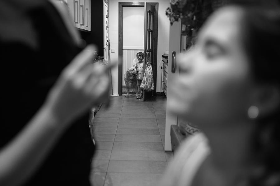 el sobrino de la novia junto a su perro, mira a la novia mientras la maquillan