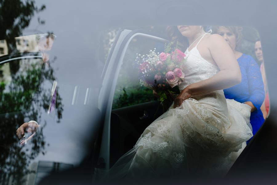fotografía creativa de la novia entrando en el coche camino de la ceremonia