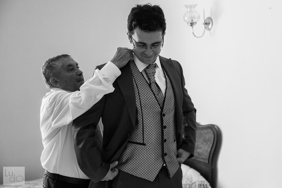 foto del novio mientras su padre le ayuda a colocarse la chaqueta