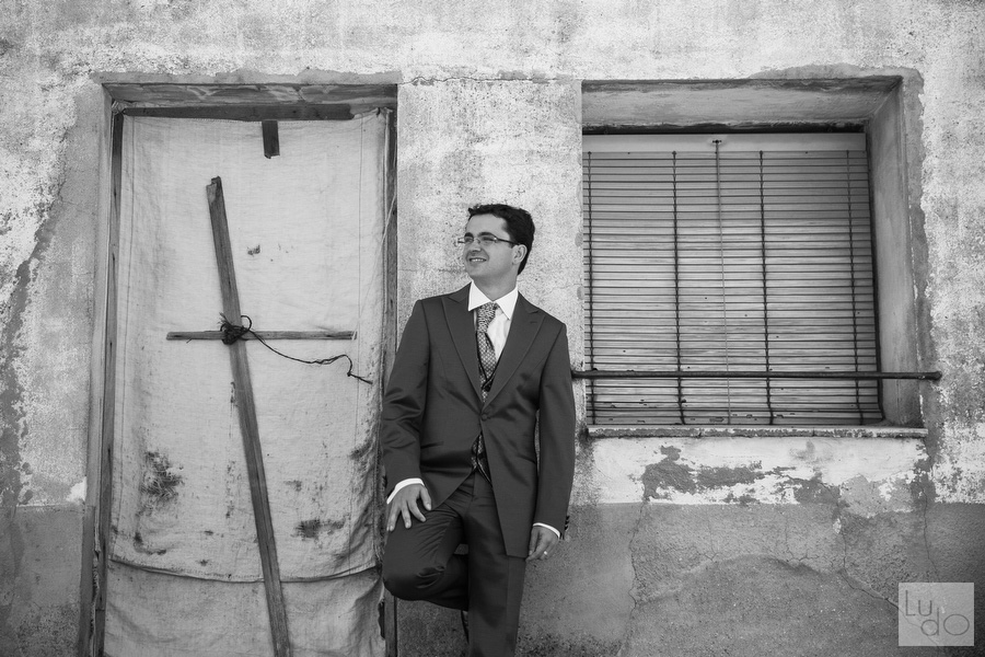 foto del novio vestido de traje sonriente frente a la fachada de la casa de sus abuelos en mozoncillo