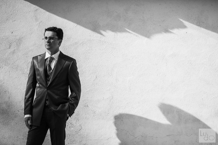 foto casual del novio utilizando las sombras que provoca la luz del sol para darle estilo