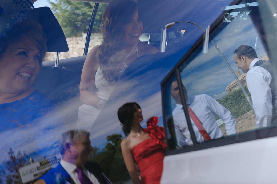 foto de la novia y su madre dentro del coche, su padre y hermanos se reflejan en el cristal
