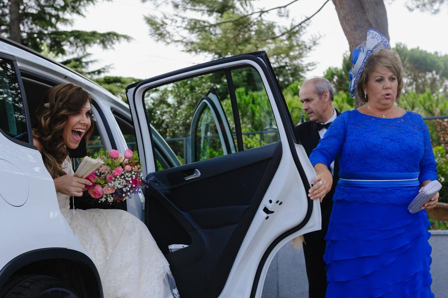 foto de la novia saliendo del coche ayudada por su madre, la novia muestra expresion de sorpresa
