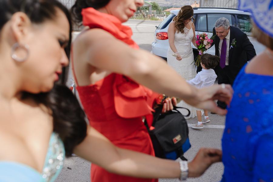 las cuñadas de la novia ayudan a la madre de la novia, mientras la novia saluda a su pequeño sobrino junto a su padre