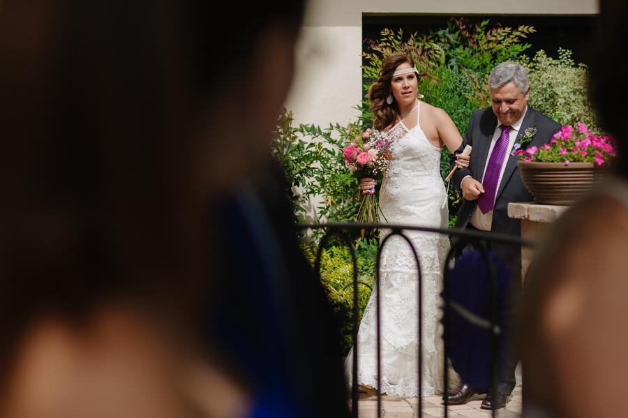 entrada de la novia del brazo de su padre con el pelo suelto al viento