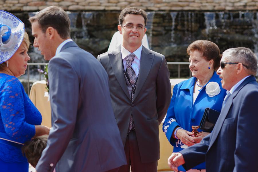 el novio en el centro junto a su padre u abuela mira la entrada de la novia con una expresion de maravillarse al verla