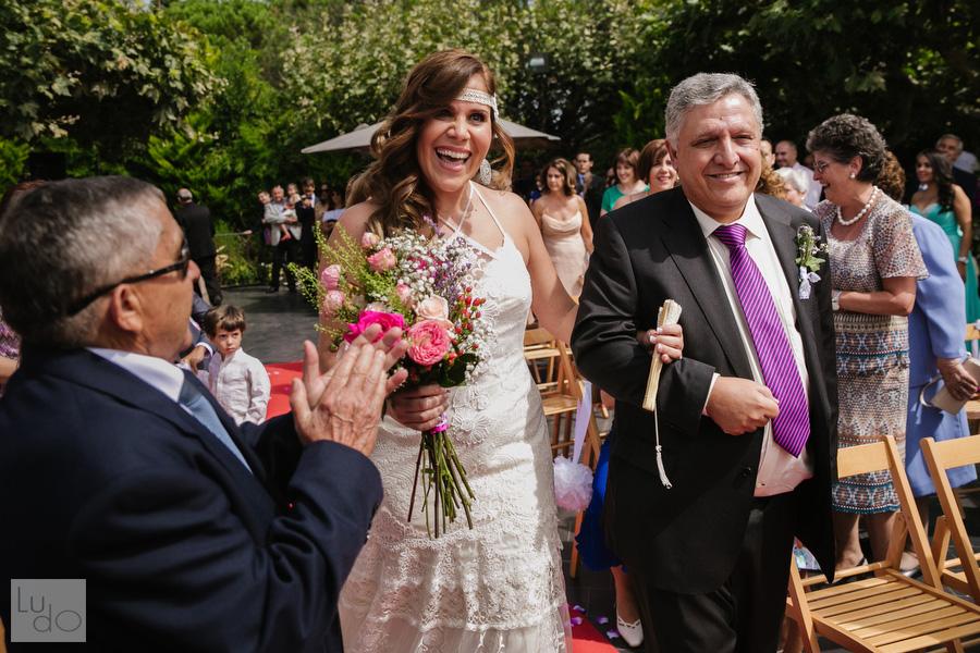 una enorme sonrisa de la novia, del brazo de su padre al llegar hasta el novio