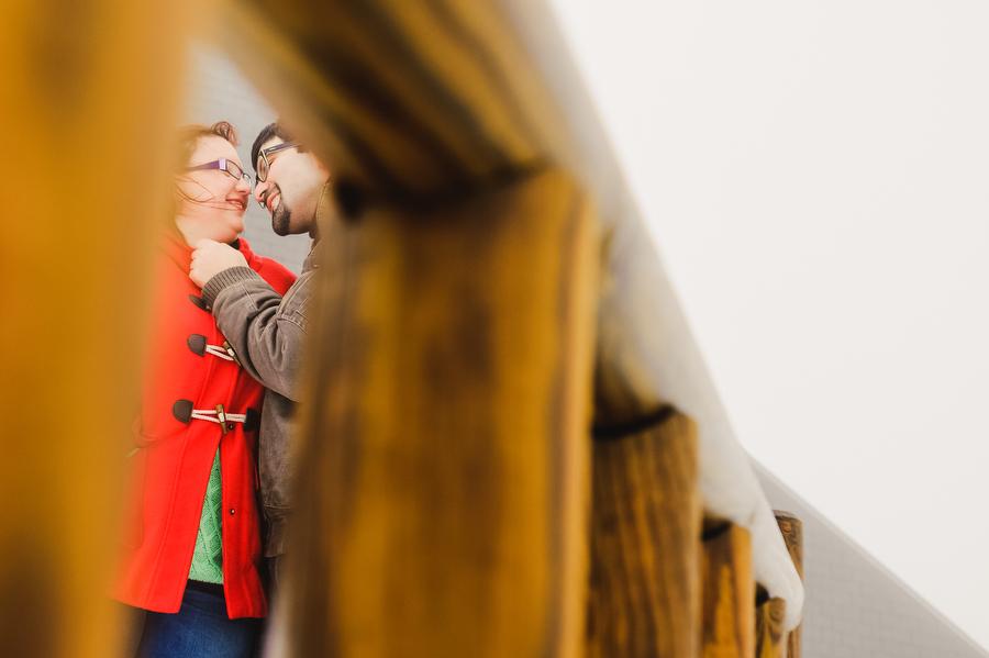 foto de pareja haciendose caricias en la cara visto a traves de una verja de madera en la estación de navacerrada